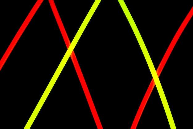 Lignes de néon rouge et jaune en diagonale sur fond noir Photo gratuit
