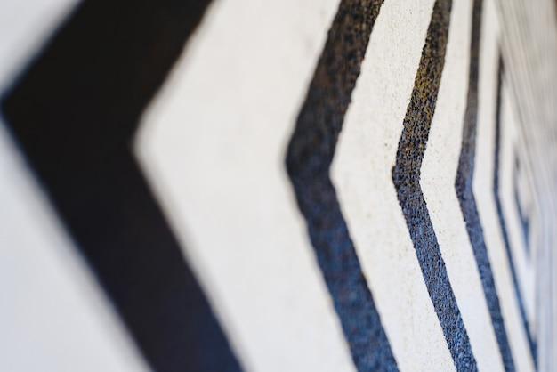 Les lignes ressemblent à des flèches noires sur fond blanc peintes sur un mur indiquant la direction. Photo Premium