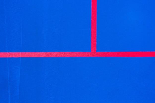 Lignes rouges traversant un sol peint en bleu de couleur intense à utiliser comme arrière-plan de conception minimaliste. Photo Premium