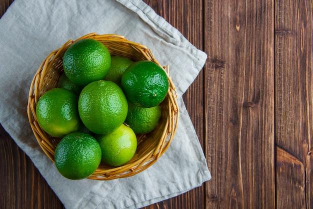 Limes Dans Un Panier En Osier Sur Bois Et Torchon De Cuisine. Pose à Plat. Photo gratuit