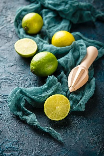Limes fraîches avec bâton de presse-agrumes. Photo Premium