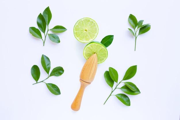Limes fraîches avec presse-agrumes en bois sur fond blanc. Photo Premium