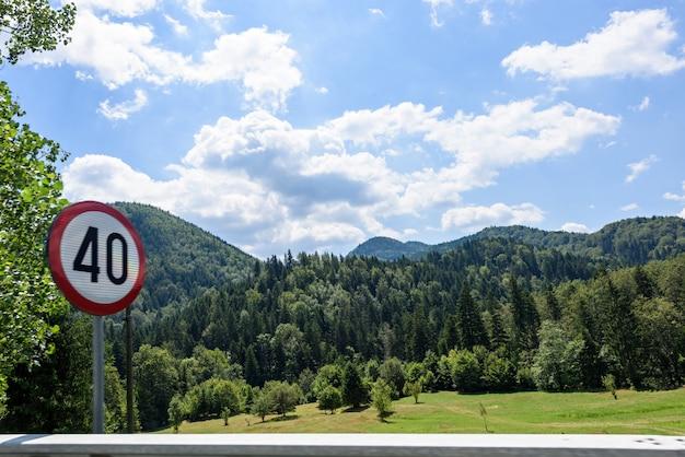 Limite de vitesse de 40 km signe de circulation et forêt verte dans les montagnes brasov le matin, roumanie Photo Premium