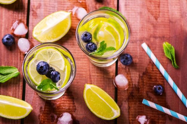 Limonade au citron vert, baies et menthe sur fond en bois Photo Premium