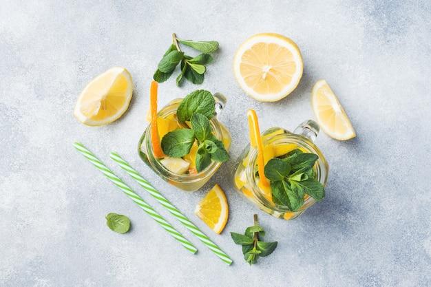 Limonade boisson de soda eau, citron et menthe feuilles en pot sur fond clair. Photo Premium