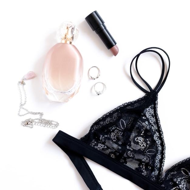 Lingerie de dentelle noire élégante, bouteille de parfum, cosmétiques et accessoires sur fond blanc Photo Premium