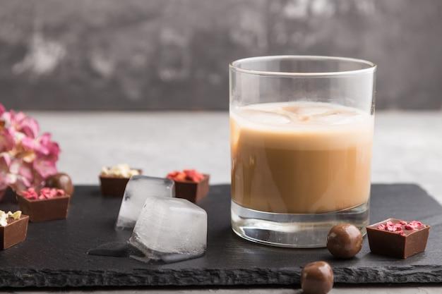 Liqueur De Chocolat Sucré Avec Glace En Verre Et Ardoise En Pierre Noire. Vue De Côté Photo Premium