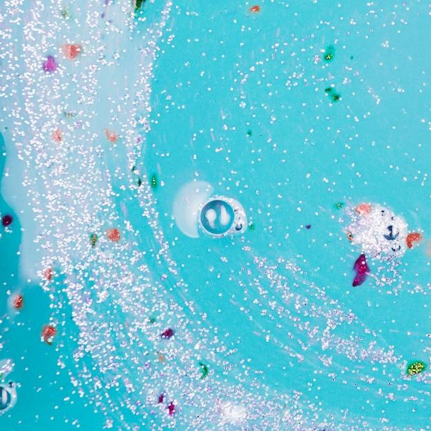Liquide bleu avec des blobs et des miettes d'argent Photo gratuit