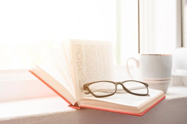 Lire un livre et boire du café Photo gratuit