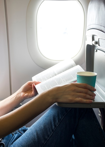 Lire Un Livre Et Tenir Une Tasse Photo gratuit