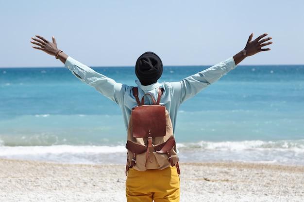 Lire La Vue D'un Homme Afro-américain Insouciant Heureux Debout Sur La Plage En Face De La Mer Azur, écartant Les Bras, Sentant La Liberté Et La Connexion à La Nature Incroyable Autour De Lui Photo gratuit