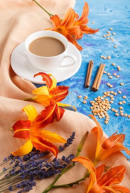 Lis Orange Et Fleurs De Lavande Et Une Tasse De Café Sur Un Fond De Béton Bleu Photo Premium