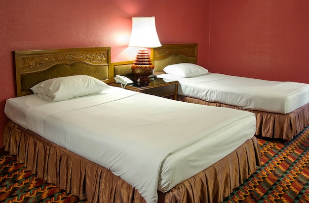 Lit double avec lampe de table dans la chambre la nuit Photo Premium