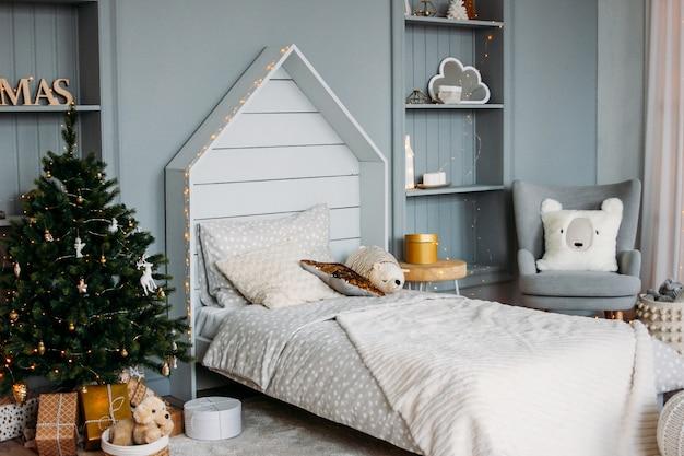 Le Lit D'enfant En Bois Blanc Avec Oreillers Et Jouets. Décor De Noël Minimaliste. Intérieur Lumineux Scandinave Photo Premium