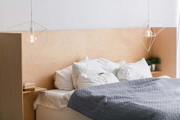 Lit noir et blanc avec tête de lit en bois à l'intérieur du loft, éclairages géométriques Photo gratuit