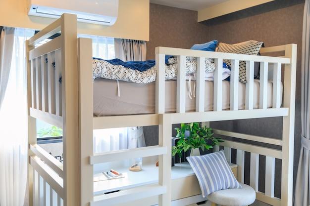 Un lit superposé en bois avec un oreiller et un climatiseur dans une chambre d'enfants. Photo Premium