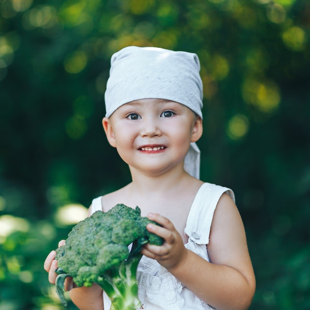 Litle heureux garçon paysan souriant en salopette blanche et bandeau gris tenant des brocolis biologiques dans les mains Photo Premium