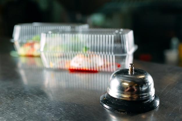 Livraison De Nourriture. Table De Distribution Dans Un Restaurant Avec Une Cloche En Métal. Nourriture Dans Des Contenants En Plastique. Panna Cotta Et Salade De Légumes Dans Des Contenants Jetables En Plastique. Photo Premium