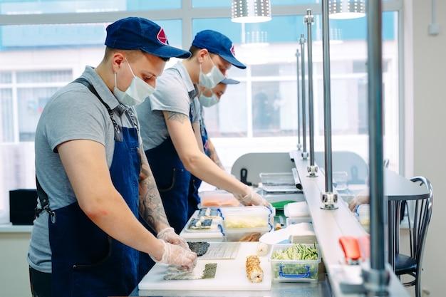Livraison De Sushi. Des Chefs Masqués Et Gantés Préparent Des Sushis Dans La Cuisine Du Restaurant. Photo Premium