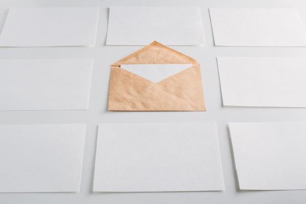 Livre blanc feuilles vides cartes et enveloppe kraft sur fond blanc. Photo Premium