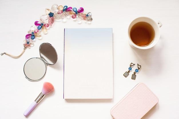 Livre blanc isolé sur fond de bois texturé blanc avec accessoires femmes mignonnes Photo Premium