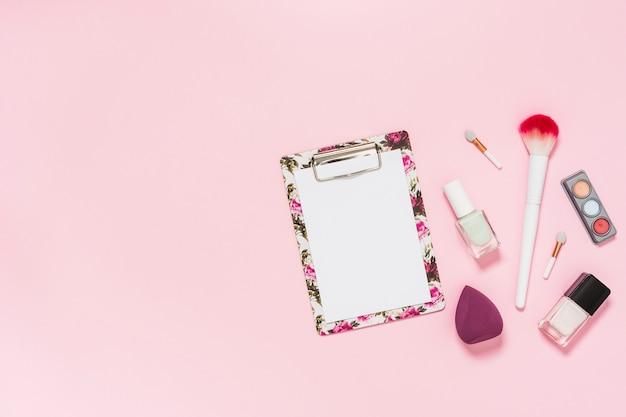 Livre blanc sur le presse-papiers avec un pinceau de maquillage; bouteille de vernis à ongles; palette d'ombres à paupières et mixeur sur fond rose Photo gratuit