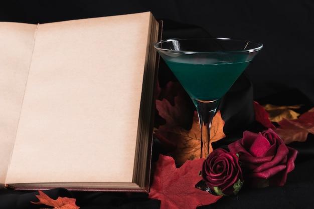 Livre avec boisson verte et roses Photo gratuit