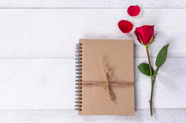 Livre de bricolage noué avec une corde de chanvre décorée de rose rouge et de pétales sur une table en bois blanche Photo Premium