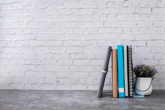 Livre et cahier papier sur le mur de briques de la maison. Photo Premium