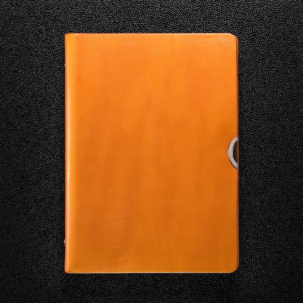 Livre en cuir orange sur fond sombre. vue de face du livre à couverture rigide. Photo Premium