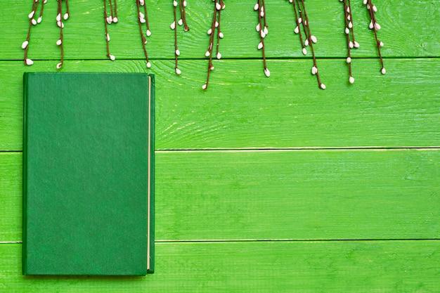 Un livre dans une couverture verte dure sur un fond en bois vert et des branches de saule. vue de dessus. espace de copie Photo Premium
