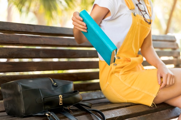 Livre d'école adolescente plaçant sur un banc Photo gratuit