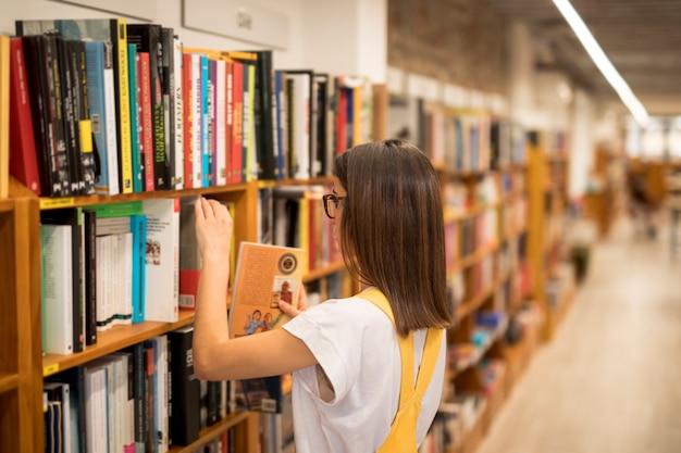 Livre d'écolière adolescent ramasser de l'étagère Photo gratuit
