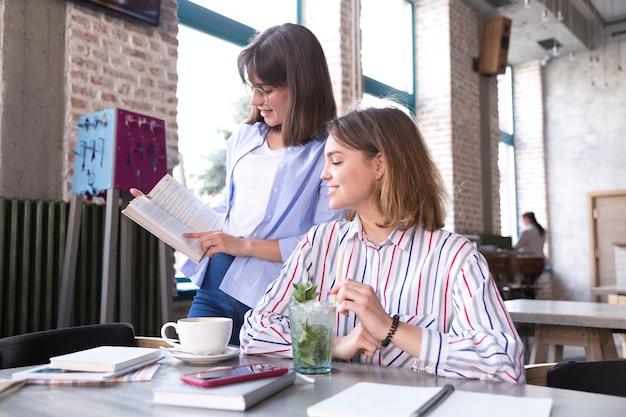 Livre de femmes discutant dans un café Photo gratuit