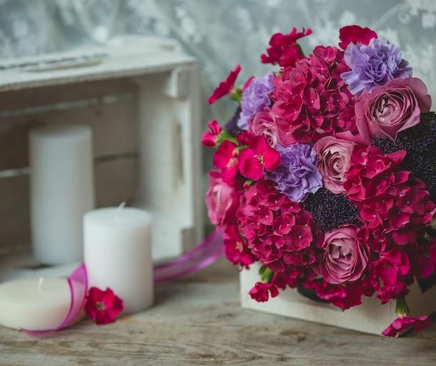 Livre de fleurs rouges debout sur un livre et des bougies autour d'une table Photo gratuit