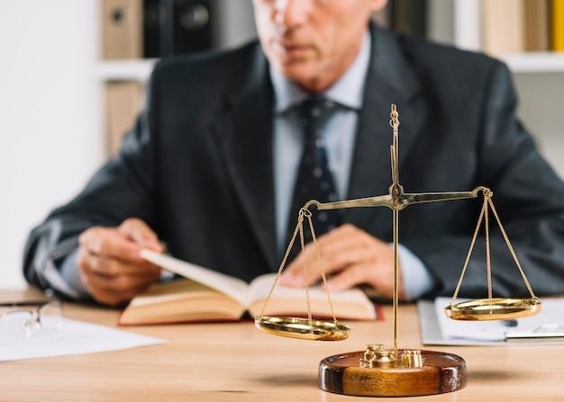 Livre de lecture d'avocat mâle mature avec l'échelle de la justice sur le bureau Photo gratuit
