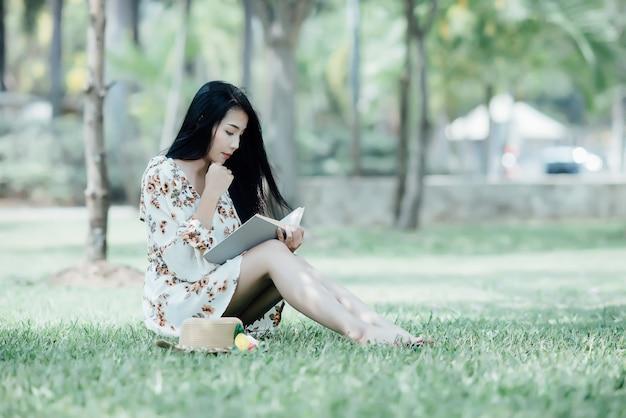 Livre De Lecture De Belle Fille Au Parc En Lumière Du Soleil De L'été Photo gratuit