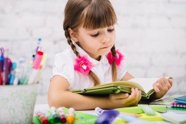 Livre de lecture concentré pour enfants à la table Photo gratuit