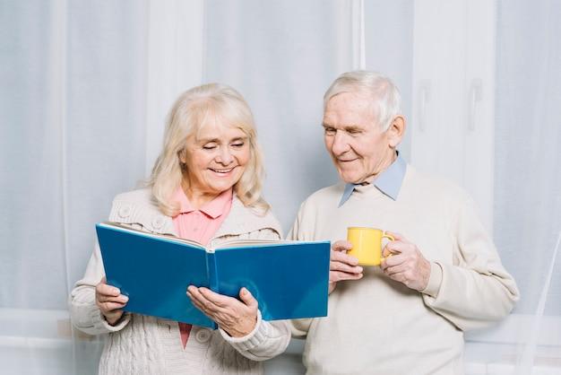 Livre de lecture de couple de personnes âgées Photo gratuit