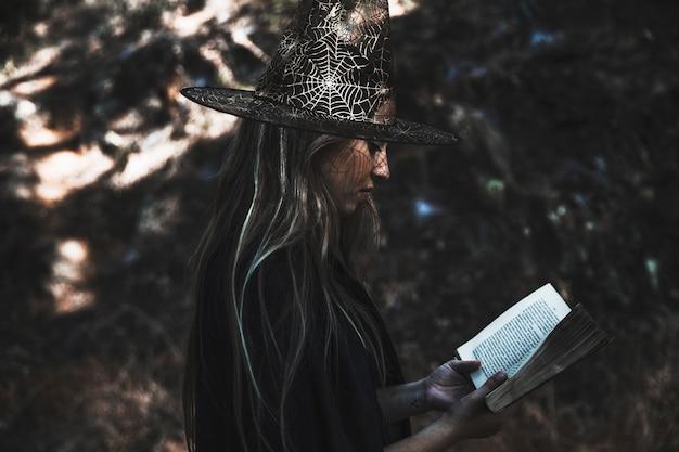 Livre De Lecture De Dame En Costume De Sorcière Photo gratuit