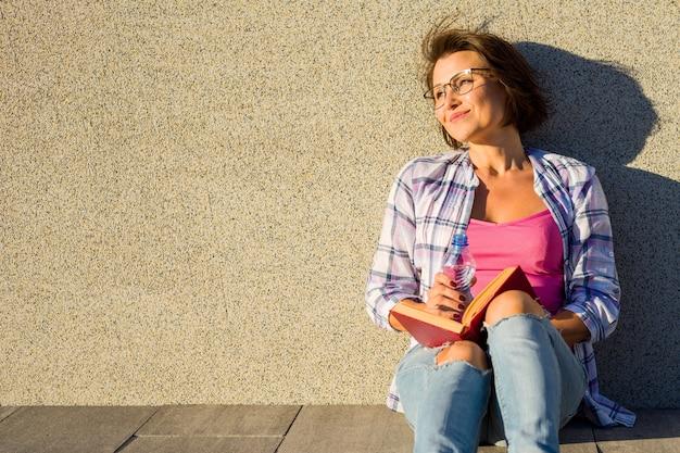 Livre de lecture d'eau potable femme souriante. Photo Premium
