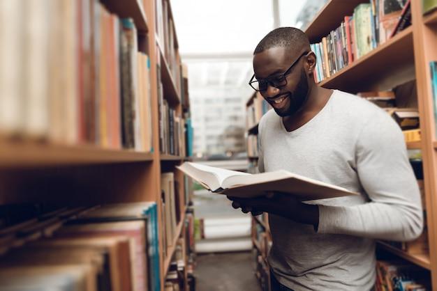 Livre de lecture ethnique afro-américain dans la bibliothèque. Photo Premium