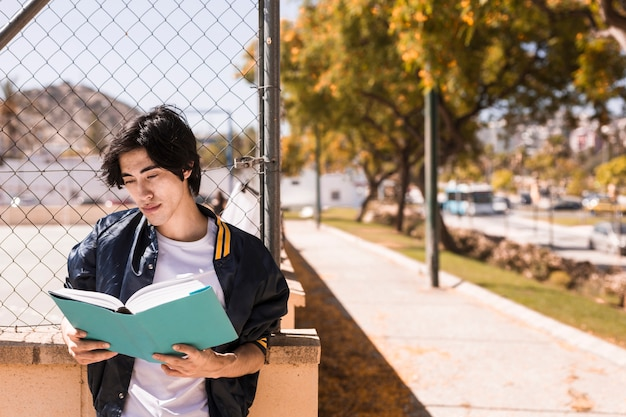 Livre de lecture ethnique garçon soigneusement Photo gratuit