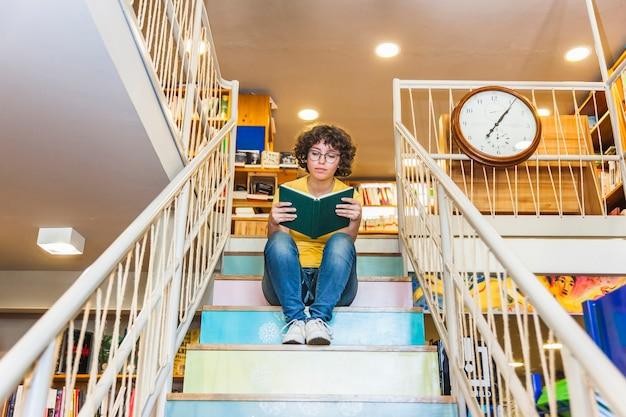 Livre de lecture féminine croustillante assis sur les marches. Photo gratuit