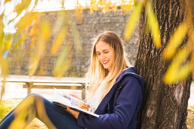 Livre de lecture féminine séduisante sous la couronne d'arbre d'automne Photo gratuit