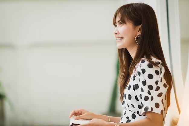 Livre de lecture de femme asiatique avec bonheur dans le temps libre Photo Premium