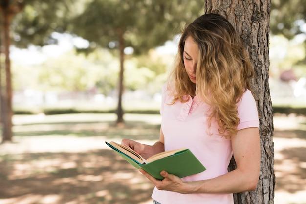 Livre de lecture femme jeune étudiant dans le parc Photo gratuit