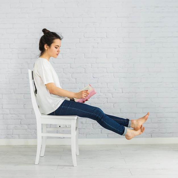 Livre de lecture de femme ludique sur chaise Photo gratuit