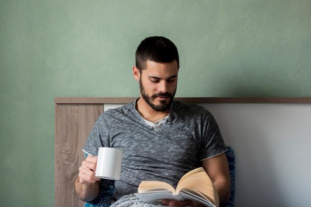 Livre de lecture homme barbu et tenant la tasse Photo gratuit