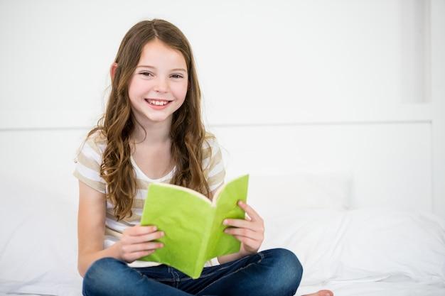 Livre De Lecture De Jolie Fille Heureuse Sur Le Lit Photo Premium